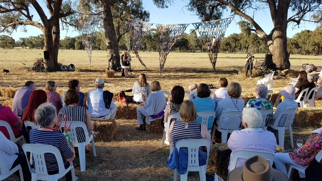 Women sitting in an open paddock listing to guest speakers